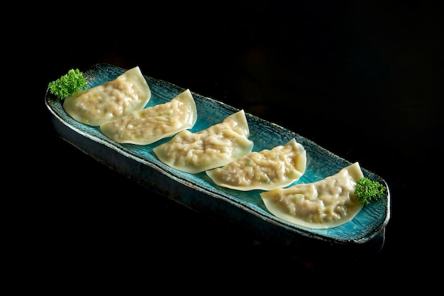 Gyoza asiatique alléchant farci de viande, servi sur une assiette bleue.