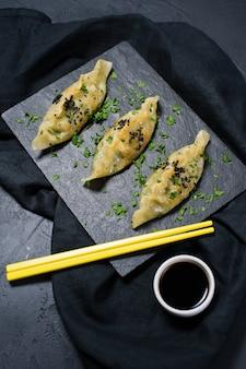 Gyoza japonais frit sur un plateau en pierre noire, baguettes jaunes.