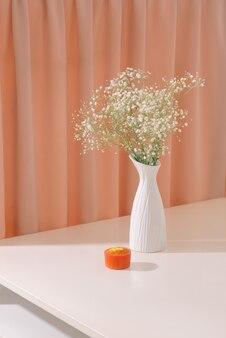Gypsophila (fleurs de gypsophile), en bouteille sur fond texturé. belles masses légères et aérées de petites fleurs blanches. nature morte florale comme concept de décoration d'intérieur.