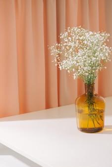 Gypsophila (fleurs de gypsophile), en bouteille de verre sur fond texturé. belles masses légères et aérées de petites fleurs blanches. nature morte florale comme concept de décoration d'intérieur.