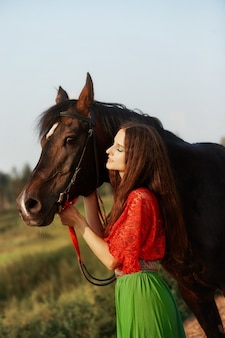 Gypsy girl monte un cheval dans un champ en été. une femme aux cheveux longs caresse et caresse un cheval debout dans l'herbe verte