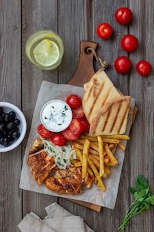 Gyros plat grec avec poulet, frites, tomates, oignons et pita. cuisine grecque.