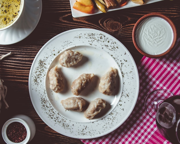 Gyurza sur une assiette blanche avec du sumac et de la crème sure