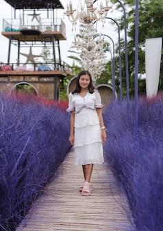 Haappy asian woman walking sur pont de bois entre jardin d'automne herbe sèche violet coloré