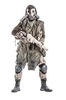 Habitant survivant de contaminé par une catastrophe nucléaire ou un monde dangereux de pollution chimique, en lambeaux et masque à gaz, debout avec une arme à feu à la main, isolé sur fond blanc shoot studio