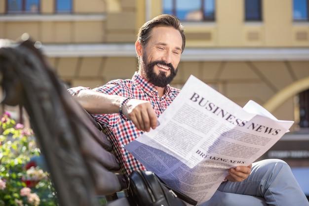 L'habitude du matin. agréable homme adulte souriant lisant un journal alors qu'il était assis sur le banc
