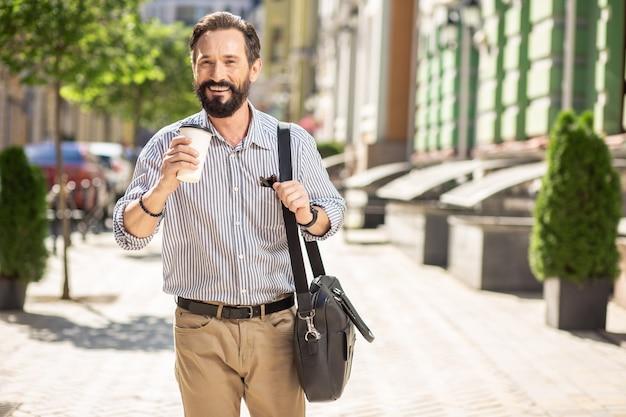 L'habitude du matin. enthousiaste barbu marchant le long de la rue tout en buvant du café