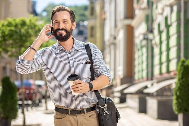 Habitude quotidienne. enthousiaste bel homme buvant du café tout en parlant au téléphone le matin