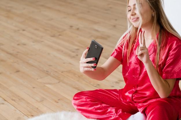 Habitude de selfie. dépendance au smartphone. jeune femme en pyjama montrant le signe v.