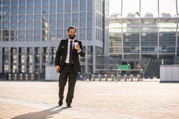 Habitude de tous les jours. enthousiaste homme d'affaires barbu va travailler tout en buvant du café