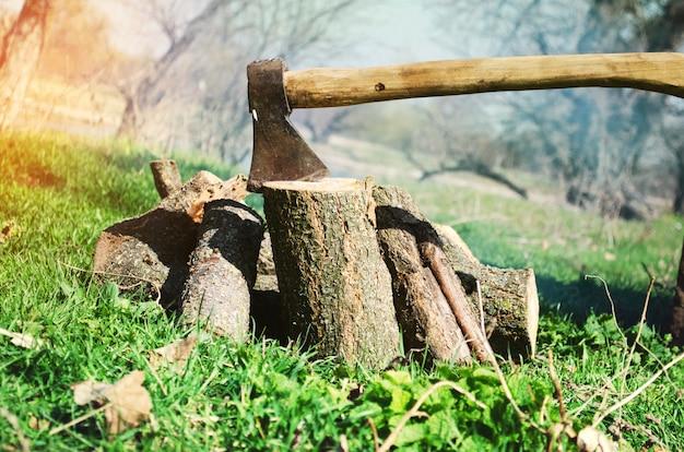 Hache et bois de chauffage sur l'herbe verte