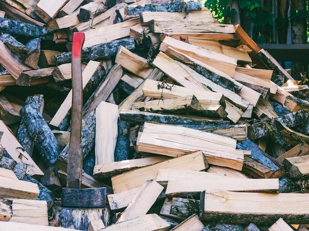 Hache couperet et un tas de charme de hêtre haché et bois de chauffage de frêne pour le poêle et la cheminée