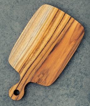 Hacher la planche à découper en bois de teck sur fond de pierre sombre.