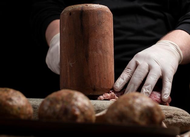 Hacher de la viande crue avec un marteau en bois