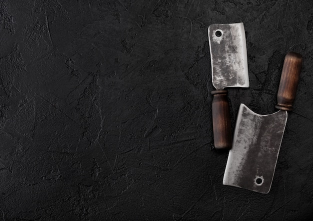 Haches de couteau à viande vintage sur table en pierre noire.