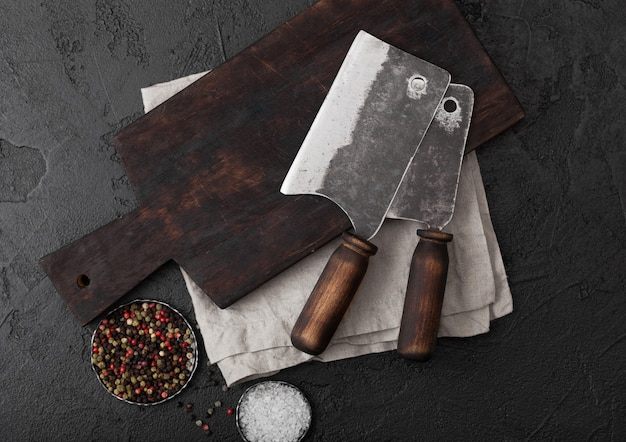 Hachette de couteau à viande vintage sur planche à découper vintage et table en pierre noire.