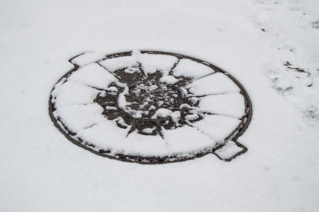 Hachures couvrent les eaux usées municipales recouvertes de première neige