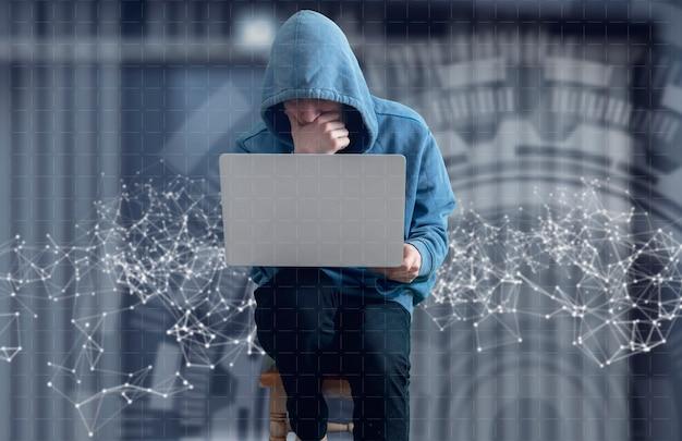 Un hacker anonyme dans le capot avec un ordinateur, une rupture des informations numériques