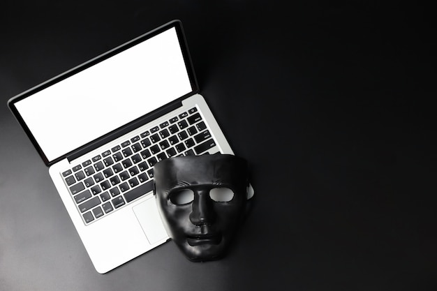 Hacker et cyber crime concept, masque noir sur nouvel ordinateur avec écran blanc sur fond noir