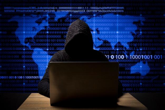 Hacker dans une veste avec une capuche avec un ordinateur portable est assis à la table