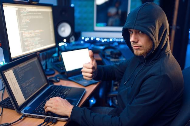 Hacker in hood montre le pouce levé sur son lieu de travail avec un ordinateur portable et un pc, un mot de passe ou un piratage de compte. espionnage internet, mode de vie criminel, travail à risque, criminel de réseau