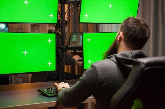 Hacker international planifiant une cyber-attaque sur un ordinateur avec une clé de chrominance verte.