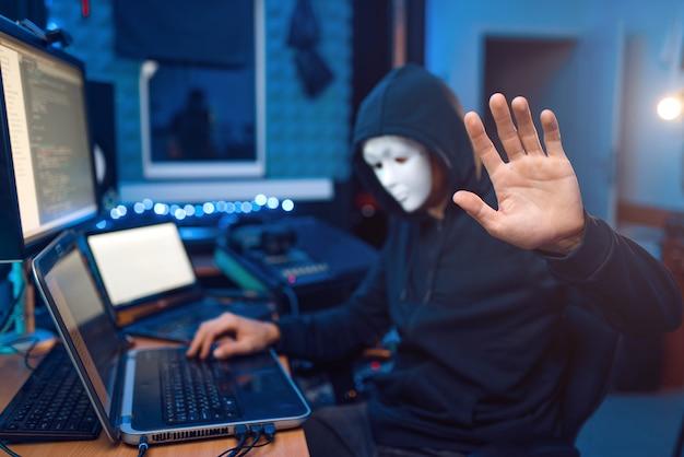 Hacker en masque et capuche assis sur son lieu de travail avec ordinateur portable et pc, mot de passe ou piratage de compte. espion internet, mode de vie illégal, travail à risque, criminel de réseau