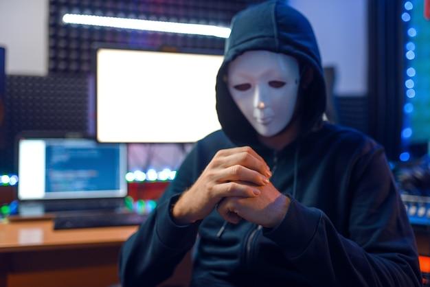 Hacker en masque et capuche assis sur son lieu de travail avec ordinateurs portables et pc, piratage d'informations. espion internet, mode de vie illégal, travail à risque