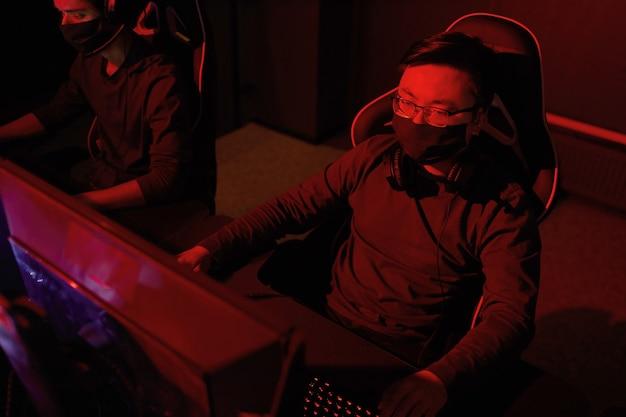 Hacker en masque de protection assis sur une chaise en face de l'écran de l'ordinateur travaillant avec un nouveau logiciel dans un bureau sombre