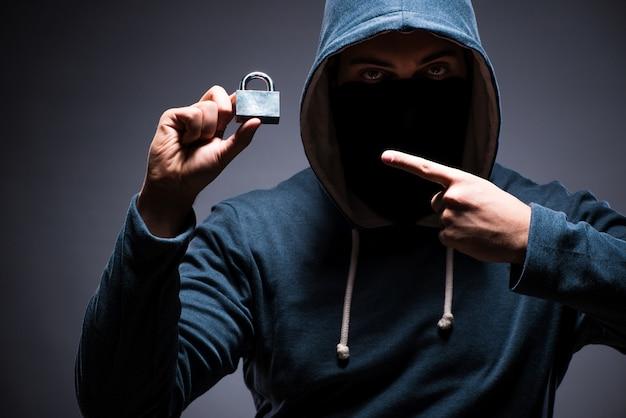 Hacker portant une cagoule dans une pièce sombre