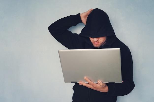 Hacker réfléchi avec son ordinateur pensant sur fond bleu. hacker dans un capot noir avec un ultrabook moderne gris. vol d'identité.