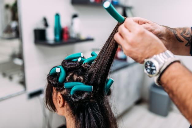 Haidresser faisant une coiffure frisée à un client.