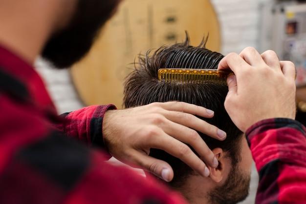 Haidresser peignant les cheveux du client