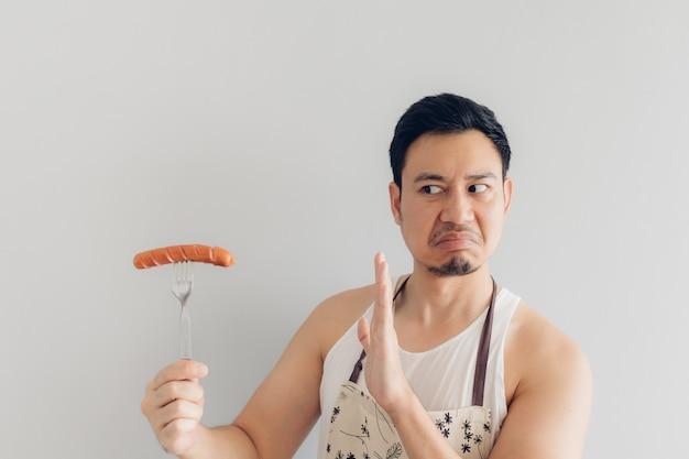 La haine du visage de l'homme a refusé de manger de la saucisse.
