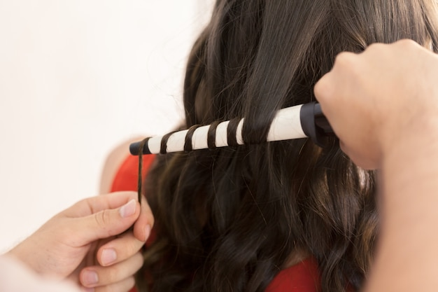 Hairstylist curling hair client dans le salon de coiffure