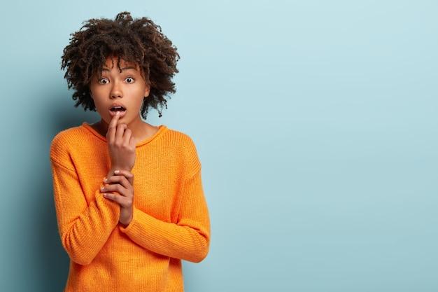 Hald length shot of impressionné surpris jeune femme afro-américaine regarde avec impatience