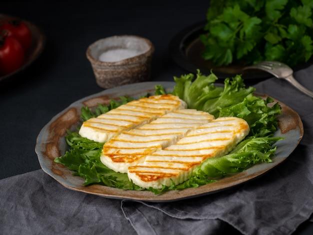 Halloumi grillé, fromage frit avec salade de laitue. régime équilibré sur fond sombre, vue de côté