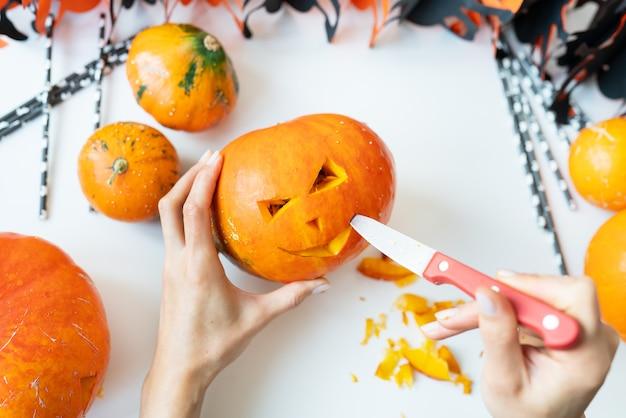 Halloween le 31 octobre. le processus étape par étape de la sculpture d'une citrouille. la fille coupe le visage de la citrouille avec un couteau. vue d'en-haut.
