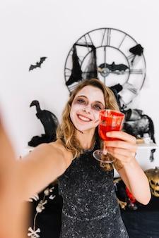 Halloween adolescente avec un verre rouge avec du faux sang