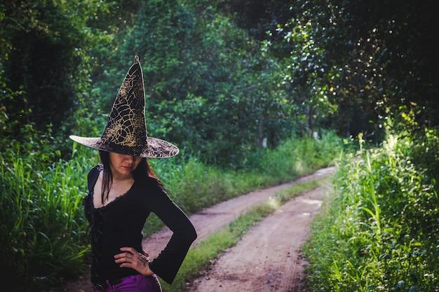 Halloween art design, belle jeune femme au chapeau de sorcière dans la forêt