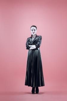 Halloween belle femme avec un maquillage d'halloween noir brillant dans un cuir noir