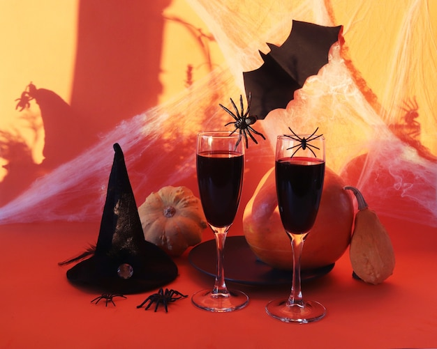 Halloween boit des araignées et des toiles d'araignées de citrouilles de vin rouge sur fond orange