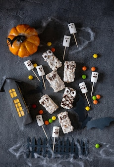 Halloween candy bar monstres drôles faits de biscuits au chocolat et fantômes guimauve gros plan sur la table. décoration de fête d'halloween. tromper ou traiter le concept.