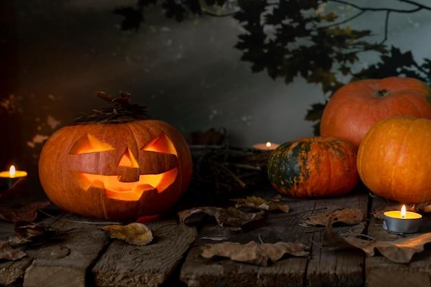Halloween citrouilles tête jack o lanterne et bougies sur table en bois dans une forêt mystique pendant la nuit. conception de halloween