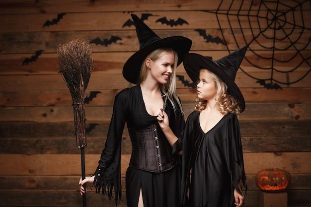 Halloween concept - mère joyeuse et sa fille en costumes de sorcière célébrant halloween posant avec des citrouilles courbées sur les chauves-souris et la toile d'araignée sur fond de studio en bois.