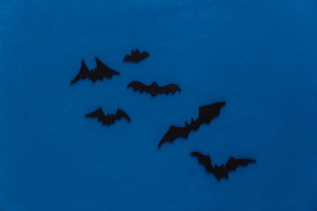 Halloween, décorations et concept effrayant. les chauves-souris noires survolent la nuit bleue