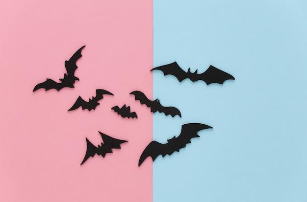 Halloween, décorations et concept effrayant. les chauves-souris noires volent sur le bleu rose