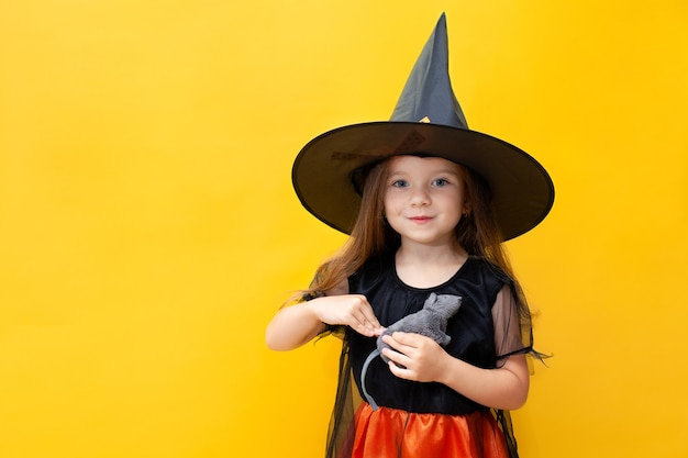 Halloween. une drôle de fille en costume de sorcière tient un rat. fond jaune, espace pour le texte. portrait émotionnel. photo de haute qualité