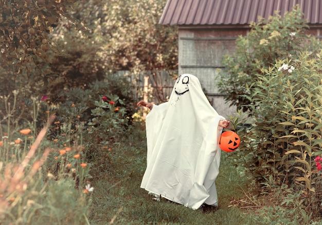 Halloween enfant habillé en costume de fantôme avec citrouille orange dans la nature à l'extérieur grimace souriante drôle