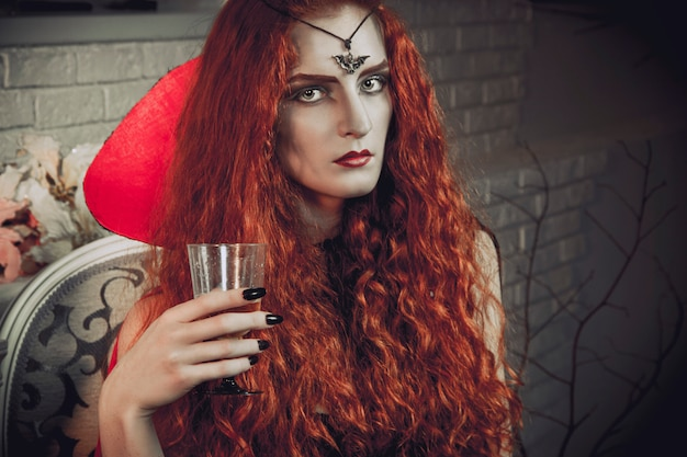Halloween femme sorcière se prépare pour la fête des morts. mage noir femelle aux cheveux roux